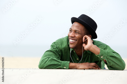 Man smiling and listing to music outdoors