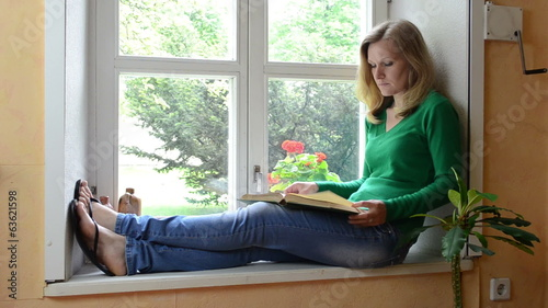 serious face woman sit on sill watch window and read book
