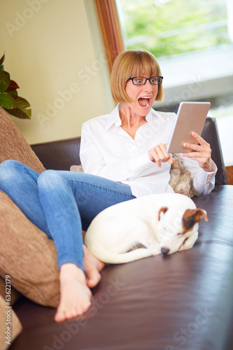 40s Woman with pad and dog on leather sofa, surprised
