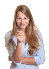 Junge Frau mit blauer Bluse zeigt zur Kamera