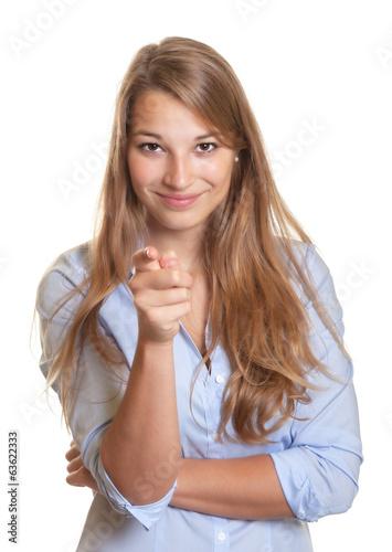 Leinwandbild Motiv Junge Frau mit blauer Bluse zeigt zur Kamera