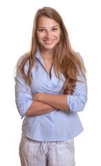 Stehende junge Frau mit blauer Bluse lacht zur Kamera