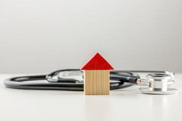 Stethoscope with a wooden model of a house