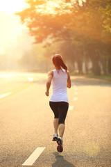 Runner athlete running on sunrise road