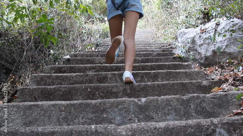 woman climb on stairs to the top of mountain