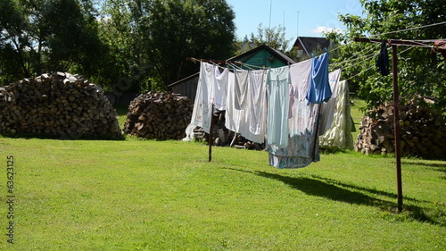 laundry dry on outdoor rope move in wind and firewood stacked