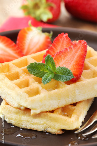 Stack of Belgian waffles with fresh strawberries