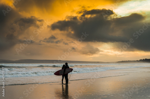 A surfing couple on the beach.