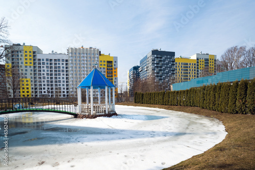 Urban landscape with a pond and pergola in winter.
