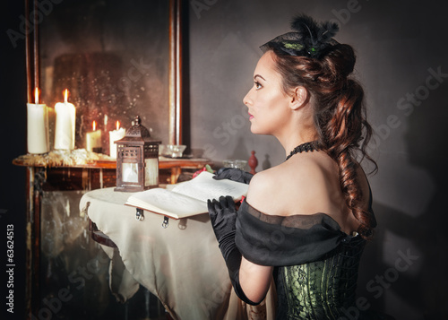 Beautiful woman in medieval dress near mirror