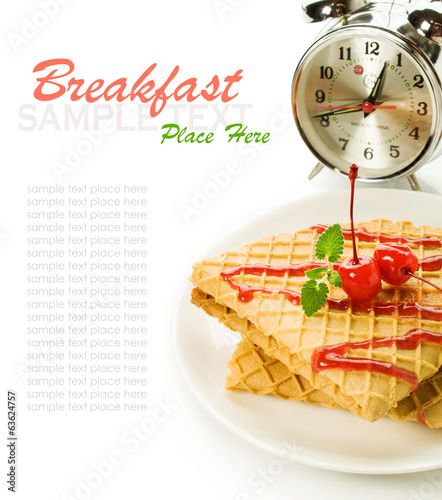 waffles with cherry topping and alarm clock isolated on white