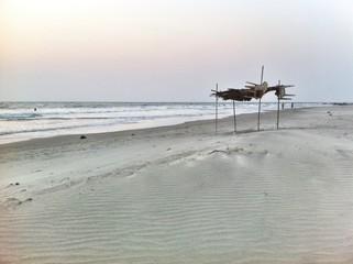 bamboo summer tent on the empty beach in sunset Goa