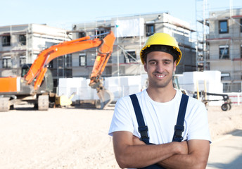 Lachender Bauarbeiter mit rotem Bagger