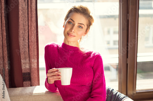 Portrait of beautiful woman with a white cup