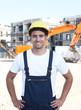 Stehender Bauarbeiter mit rotem Bagger im Hintergrund