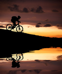 silhouette of mountain biker with Reflection and sunset