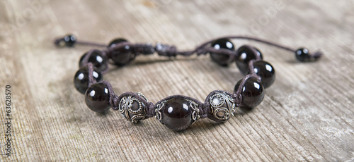 Popular Buddhist bracelet shamballa on a wooden background