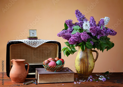 Lilac in a vase, old radio and easter eggs