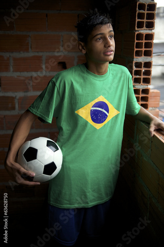 Serious Young Brazilian Soccer Player Looking Out Favela Window