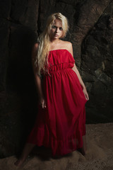 Beautiful blond woman in Red Dress.near the rock.Summer