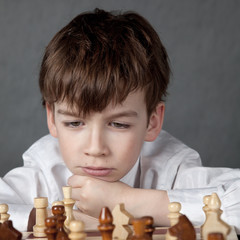 thoughtful boy playing chess, studio
