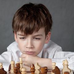 thoughtful boy playing chess, studio