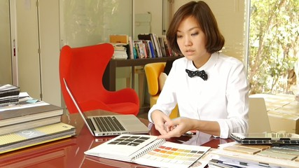 Woman working with color samples and typing on computer.