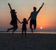 Happy beautiful family jumping on the beach at the sunset