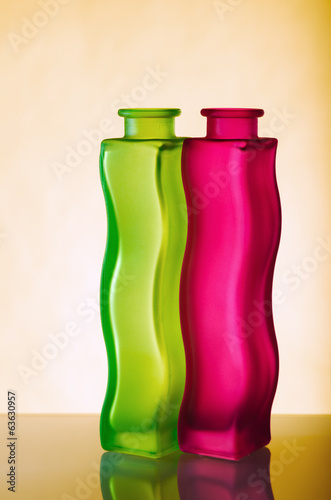 Two elegant green and red vases on a yellow background, a close