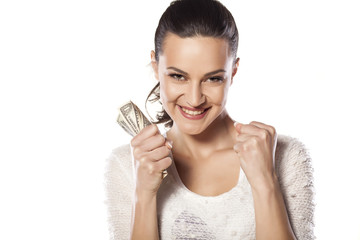 girl with the winning gesture holding money in hand