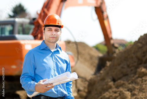 Engineer holding a blueprint in a construction site
