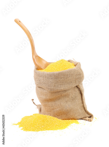 Cornmeal in burlap with wooden spoon.