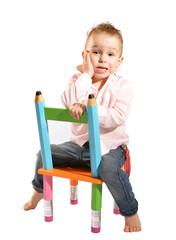 kleiner junge sitzt verkehrt herum auf einem stuhl