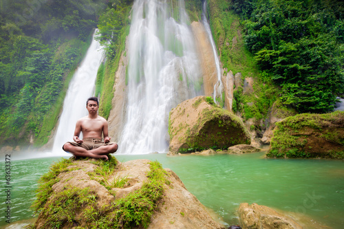 Human male Meditation in front of big waterfall