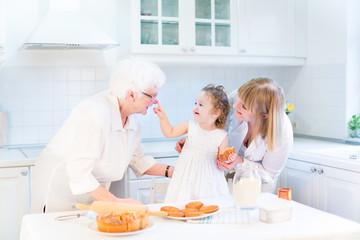 Funny toddler girl playing in kitchen, having fun baking pie