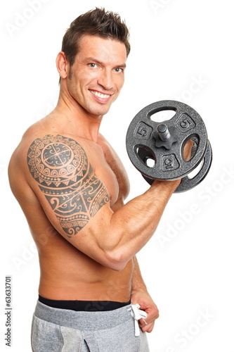 Handsome muscular man exercises with dumbbell biceps