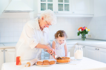Loving grandmother baking an apple pie with her adorable toddler