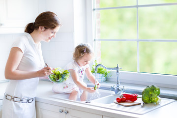 Young mother and her adorable toddler daughter cooking salad