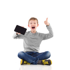 Happy young boy showing tablet