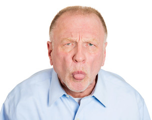 Immature older man sticking his tongue out, showing displeasure