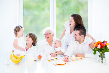 Happy young family having fun at breakfast with their grandmothe