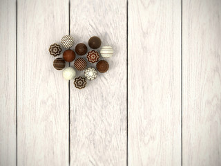 Praline Easter eggs heart on white wooden floor - top view