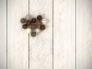 Praline Easter eggs heart on white wooden floor - top view