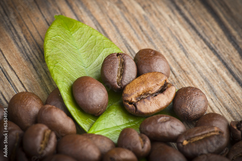 Coffee beans and leaves on the wood table