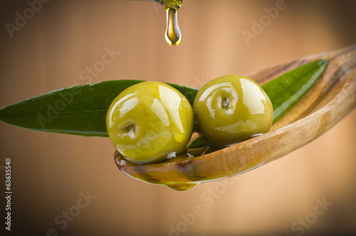 Two olives and leaves with drop oil on wood spoon