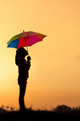 Silhouette of little girl with umbrella