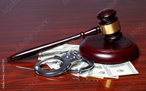 Judge Gavel and Handcuffs with Dollars Bills on the Table.