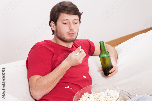Guy eating popcorn and drinking beer
