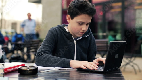 Teenager doing homework with laptop and notebook in cafe