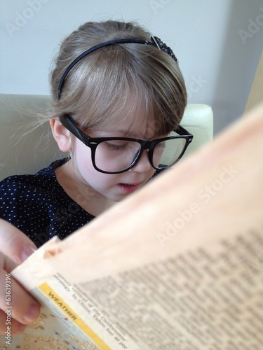 little girl reading newspaper